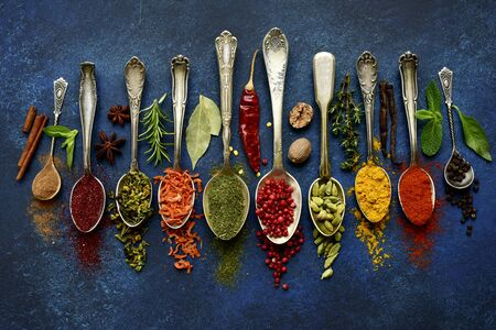 Assortment of natural spices on a vintage spoons over dark blue slate, stone, concrete or metal background.Top view with copy space. Stockfoto
