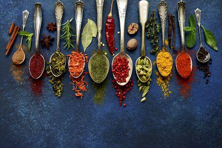 Assortimento di spezie naturali su cucchiai vintage su sfondo blu scuro di ardesia, pietra, cemento o metallo. Vista dall'alto con spazio di copia.