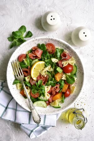 Pasta salad with vegetables and salted salmon in a bowl on a light slate, stone or concrete background. Top view with copy space.