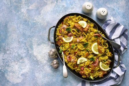 Paella - traditional dish of spanish cuisine in a skillet on a light blue slate, stone or concrete background. Top view with copy space. Фото со стока