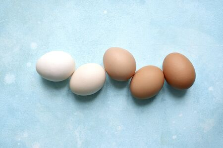 White and beige raw chicken eggs on a light blue slate, stone or concrete background. Top view with copy space.