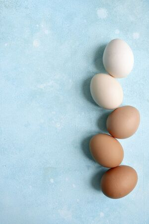 White and beige raw chicken eggs on a light blue slate, stone or concrete background. Top view with copy space. Фото со стока