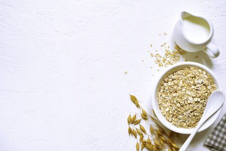 Raw organic oat flakes with milk in a white bowl over light slate, stone or concrete background - healthy breakfast. Top view with copy space. Фото со стока