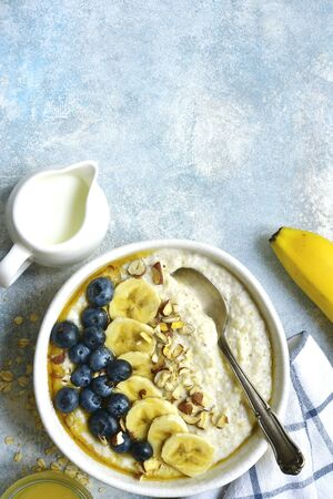 Oatmeal porridge with banana, fresh blueberry and nuts in a white bowl on a light blue slate, stone or concrete table - healthy breakfast. Top view with copy space.