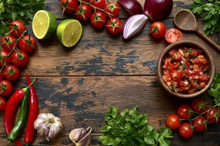 Tomato salsa (salsa roja) - traditional mexican sauce  with ingredients for making on a wooden background.Top view with copy space. Stockfoto