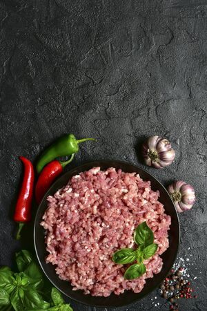Homemade minced meat in a black bowl over dark slate, stone or concrete background with ingredients for making.Top view with copy space. Stockfoto