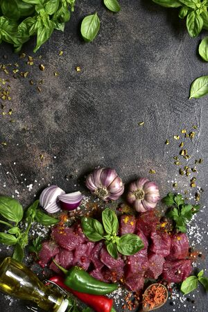 Raw meat with ingredients for making stew or ragout on a dark slate, stone, concrete or metal background. Top view with copy space.