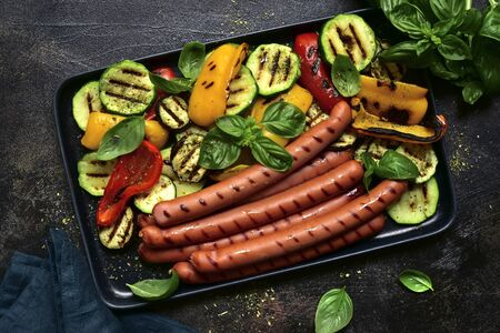 Grilled bavarian sausage with vegetables on a black dish over dark slate, stone, concrete or metal background. Top view with copy space.
