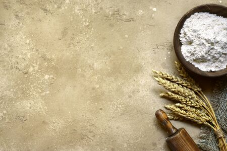 Organic wheat flour in a wooden bowl over light slate, stone or concrete background. Top ivew with copy space.