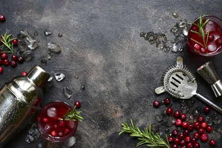 Winter christmas cocktail with cranberry and rosemary in a glasses on a dark slate, stone or concrete background. Top view with copy space. Banque d'images - 131943387
