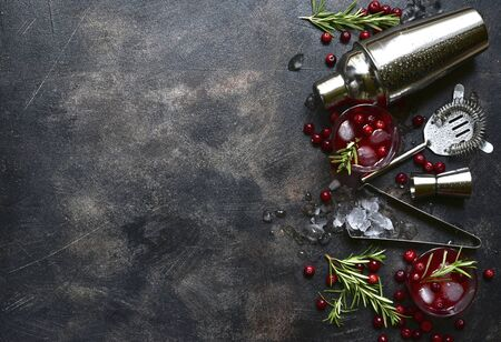 Winter christmas cocktail with cranberry and rosemary in a glasses on a dark slate, stone or concrete background. Top view with copy space. Banque d'images - 131943391