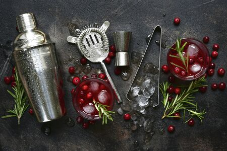 Winter christmas cocktail with cranberry and rosemary in a glasses on a dark slate, stone or concrete background. Top view with copy space. Banque d'images - 131901439