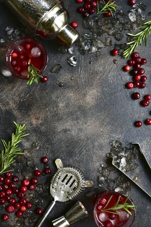 Winter christmas cocktail with cranberry and rosemary in a glasses on a dark slate, stone or concrete background. Top view with copy space. Banque d'images - 131943392
