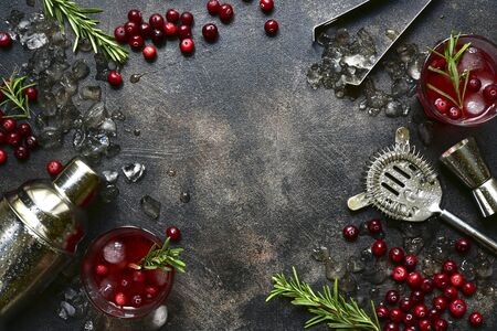 Winter christmas cocktail with cranberry and rosemary in a glasses on a dark slate, stone or concrete background. Top view with copy space. Banque d'images - 131943398