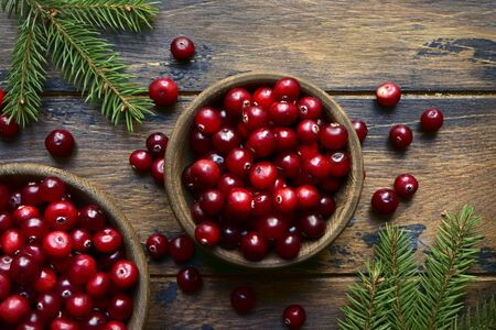 Fresh ripe cranberries in a wooden bowls on a dark rustic background. Top view with copy space.