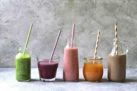 Assortment of colorful smoothies in a bottles with paper straws on a light slate, stone or concrete background.