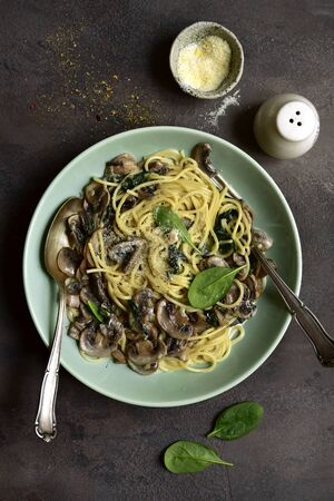 Spaghetti with mushrooms and spinach in a cream sauce in a bowl on a dark slate, stone or concrete background. Top view with copy space.