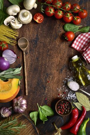 Culinary background with ingredients for making vegetarian dishes on a dark rustic wooden table. Top view with copy space.