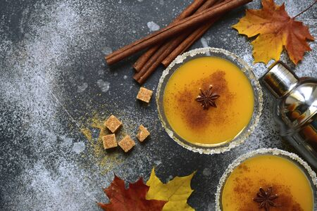 Delicious spicy pumpkin cocktail in a martini glasses on a dark slate, stone or concrete background.