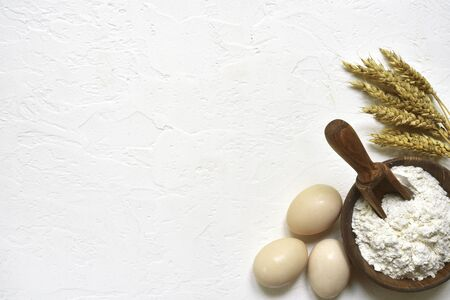 Baking background with flour, eggs and rolling pin on a white slate, stone or concrete table. Top view with copy space.