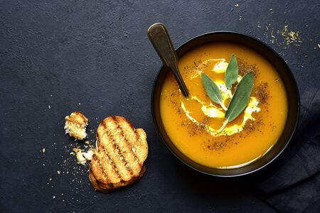 Creamy pumpkin soup with sage in a black bowl over dark slate, stone or concrete background. Top view with copy space. Фото со стока