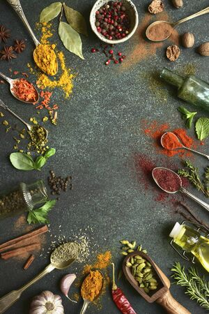 Variety of natural organic spices on a spoons on a dark green slate, stone or concrete background. Top view with copy space.