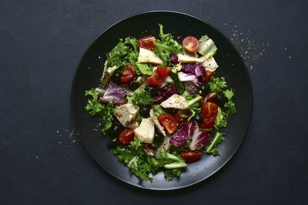Vegetable salad with chicken and spicy citrus dressing on a white plate on a dark slate, stone or concrete background. Top view with copy space.