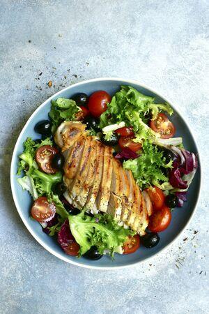 Gegrilde kip met vegetabe salade in een kom op een lichtblauwe leisteen, steen of betonnen ondergrond. Bovenaanzicht met kopie ruimte. Stockfoto