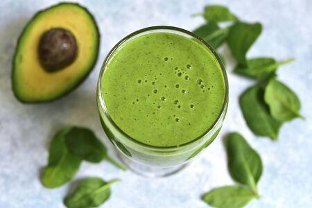 Detox green smoothie z jabłkiem, awokado i szpinakiem na jasnoniebieskim tle łupkowym, kamiennym lub betonowym. Widok z góry z miejsca na kopię.