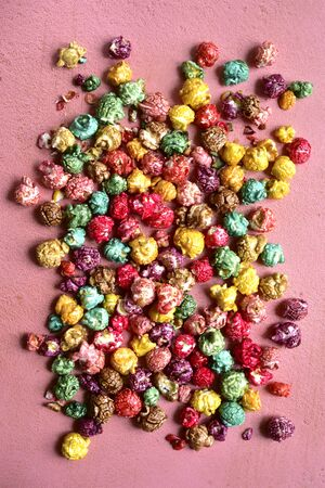 Colorful caramel candy popcorn on a pink slate, stone or concrete background. Top view with copy space. Banco de Imagens