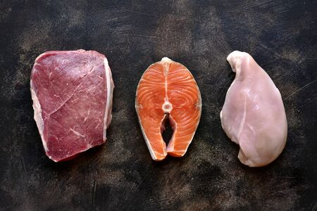 Raw marbled meat, red fish and chicken breast on a dark slate, stone or concrete background. Top view with copy space. Reklamní fotografie