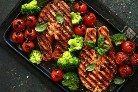 Grilled salmon steaks with vegetables on a black plate over dark green slate, stone or concrete background.Top view with copy space.