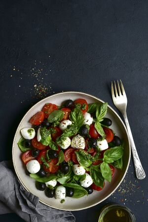 Caprese - traditional italian vegetable salad with mozzarella cheese on a plate on a black slate, stone or concrete background. Top view with copy space.