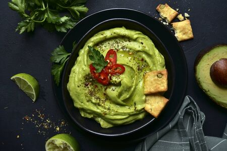 Guacamole - traditional mexican spicy avocado dip in a black bowl on a dark slate, stone or concrete background. Top view with copy space.