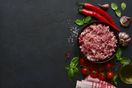 Homemade minced meat with vegetables and spices on a black slate, stone or concrete background. Top view with copy space.
