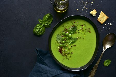 Delicious creamy green pea soup in a black bowl on a dark slate, stone or concrete background. Top view with copy space.
