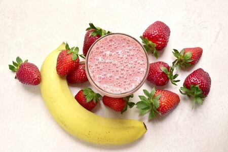 Köstlicher Erdbeer-Bananen-Smoothie in einem Glas mit Zutaten für die Zubereitung auf hellrosa Schiefer-, Stein- oder Betonhintergrund. Draufsicht mit Kopienraum.