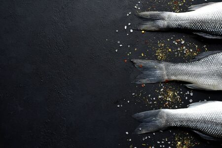 Raw fresh organic sea bass fish with spices and ingredients for making on a black slate, stone or concrete background. Top view with copy space. Stock Photo