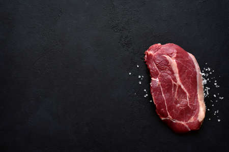 Raw organic marbled beef steak with salt and pepper on a black slate, stone or concrete background. Top view with copy space.
