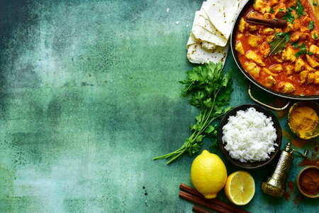 Chicken tikka masala - traditional dish of indian cuisine in a skillet over green slate, stone or concrete background. Top view with copy space.