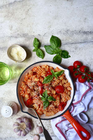 Fusilli pasta with tomatoes and garlic in a skillet. Top view with copy space.
