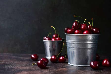 Fresh ripe organic cherry in a metal bucket on a dark slate, stone or concrete background.