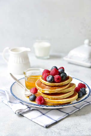 Hot banana pancakes with fresh berries and honey for a breakfast on a plate on a light background. Stockfoto