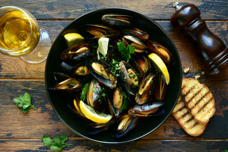 Boiled mussels with lemon and parsley in a black bowl on a rustic wooden background. Top view with copy space. 版權商用圖片