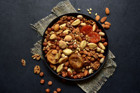 Bowl with assortment of dried fruits and nuts on a black slate, stone or concrete background. Top view with copy space.