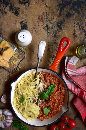 Spaghetti bolognese - traditional italian pasta with minced meat and tomatoes in a skillet pan on a rustic wooden table. Top view with copy space. Archivio Fotografico