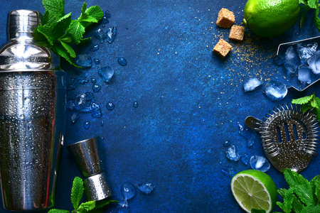 Ingredients and props for making cold summer cocktail mojito on a dark blue slate, stone or concrete background. Top view with copy space. Archivio Fotografico
