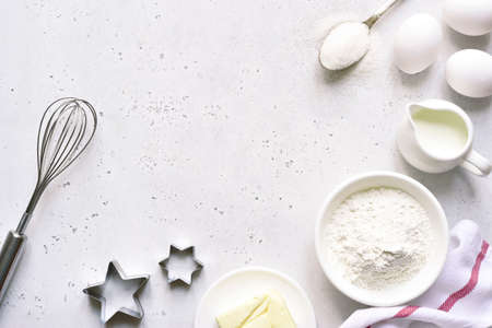 Baking background with ingredients for making cake or biscuit on a white slate, stone or concrete table. Top view with copy space. Archivio Fotografico