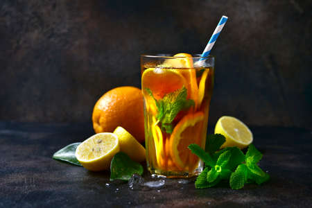 Cold citrus tea with mint in a tall glass on a dark slate, stone or concrete background.