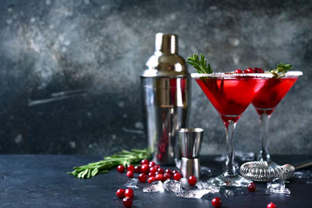 Christmas cranberry cocktail with rosemary in a glasses on a dark slate, stone or concrete background.
